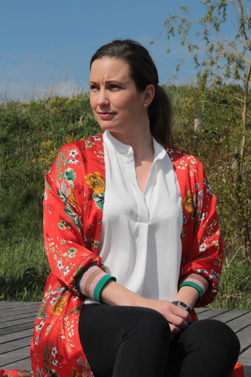 Woman sitting in red and white shirts, with grass in background