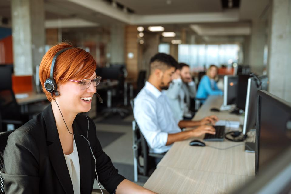 Team of business people working in a call center on the line.