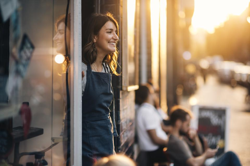 Smiling female owner looking away while standing at entrance of deli