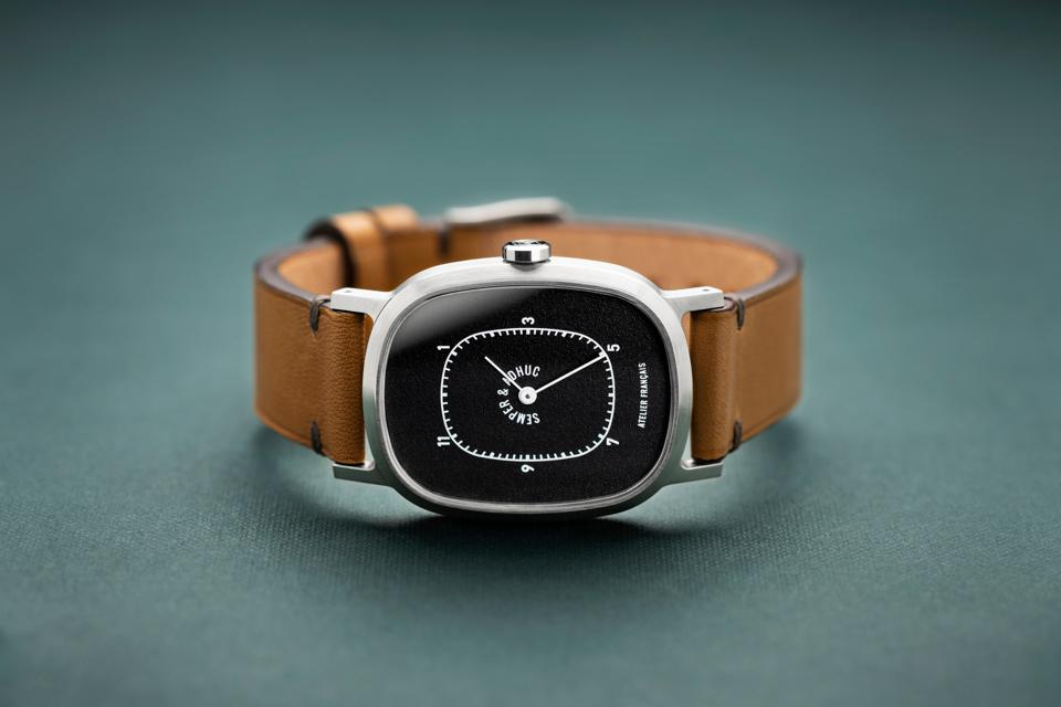 Semper & Adhuc brushed steel timepiece with black dial on leather strap.