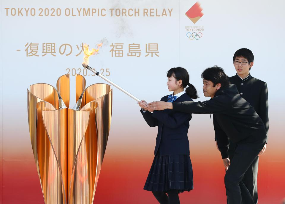 The Olympic flame is lit at the cauldron.