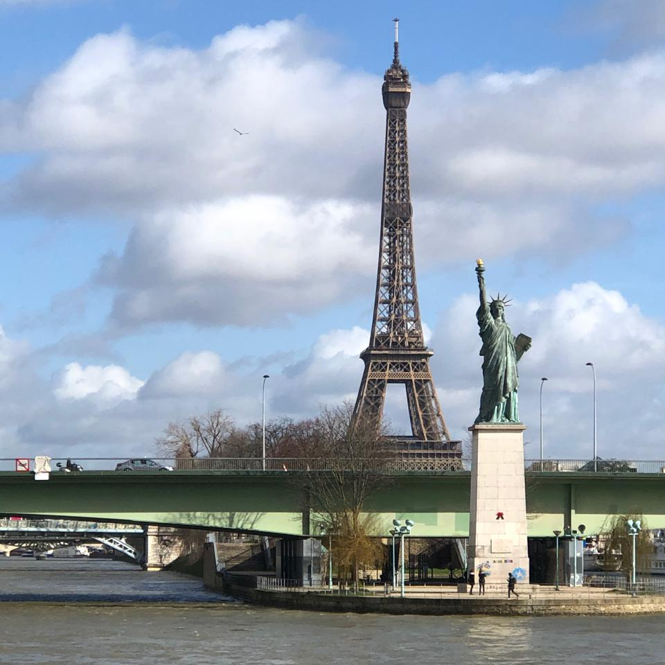 A miniature version of the Statue of Liberty stands on the Seine in front of the Eiffel Tower.