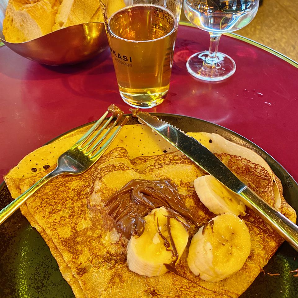 A nutella banana crepe on a plate with silverwear, glass of apple cider, bread