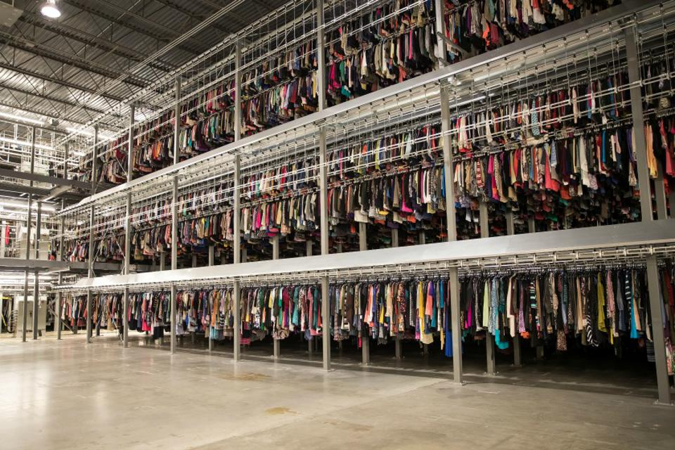 Three stories of clothing hung on racks in a warehouse.
