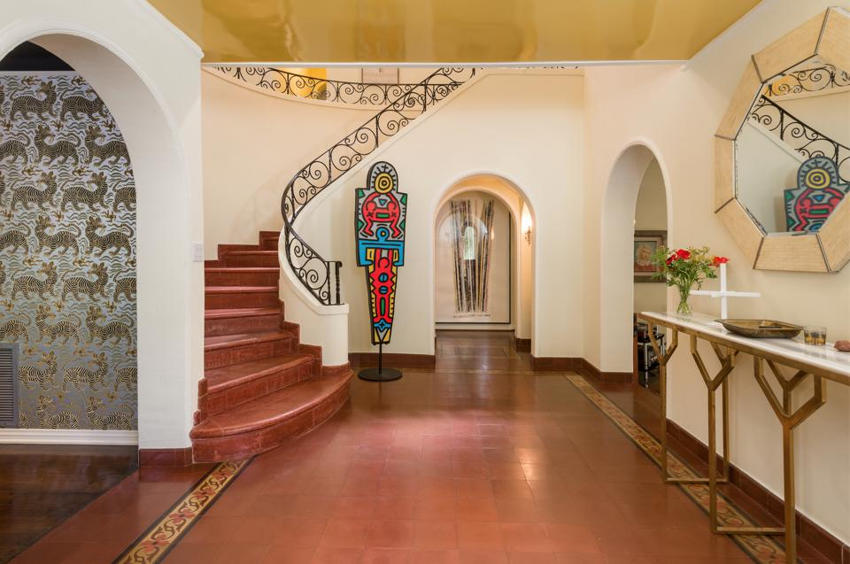 Foyer with Saltillo tile floor and grand staircase.