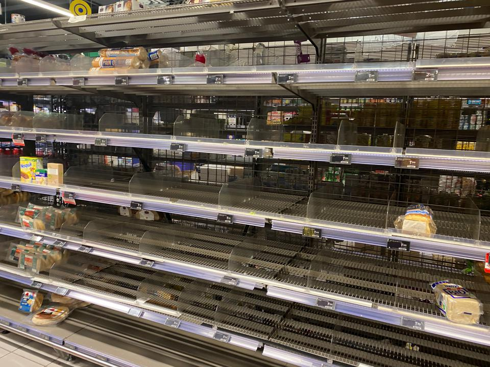 Racks and racks of a grocery story empty except for two loaves of bread.
