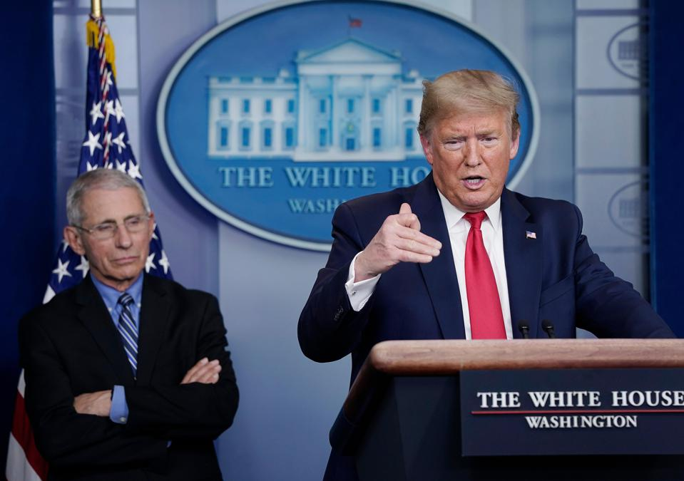 Donald Trump speaks while Dr. Anthony Fauci, director of the National Institute of Allergy and Infectious Diseases, listens