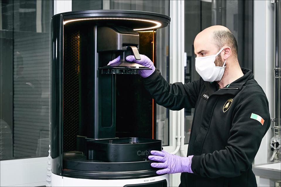Technicians in the Lamborghini R&D producing medical face shields.