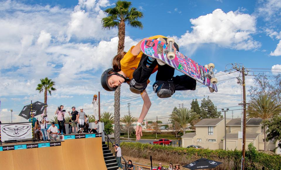 Minna Stess of Petaluma, California above a halfpipe at Vert ramp at Vans Huntington Beach