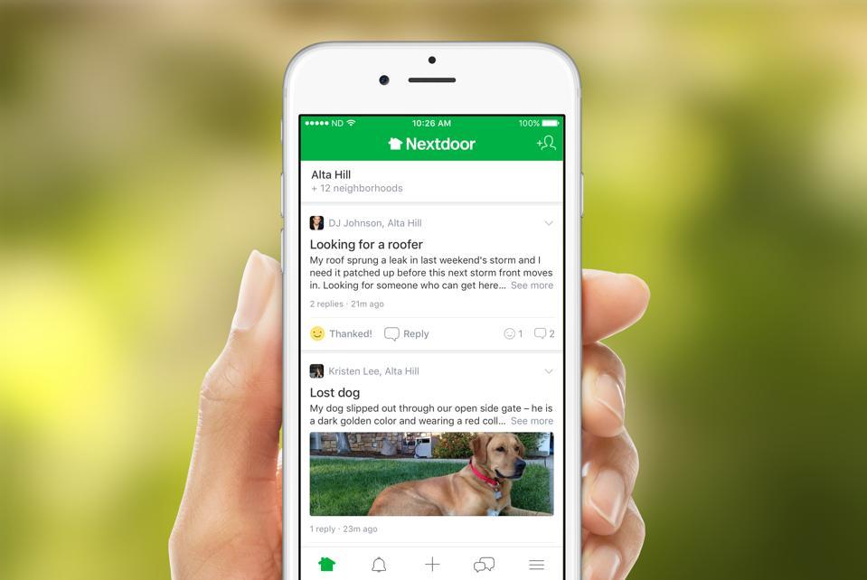 Hand holding iPhone with Nextdoor app open.
