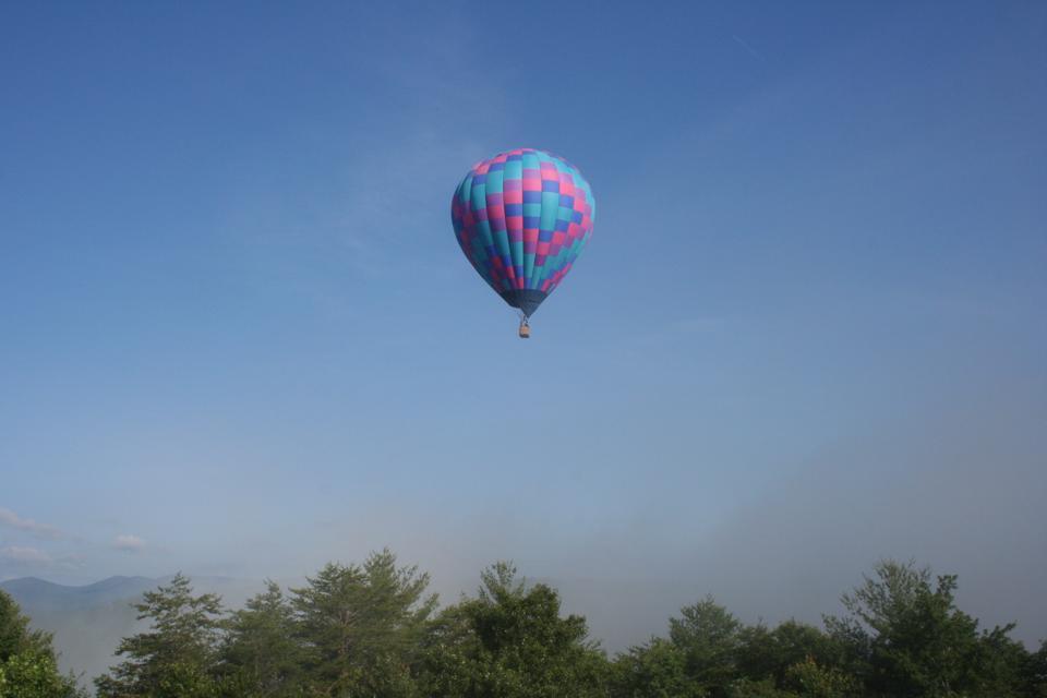 A hot air balloon rises from the mist near Anna Ruby Falls.