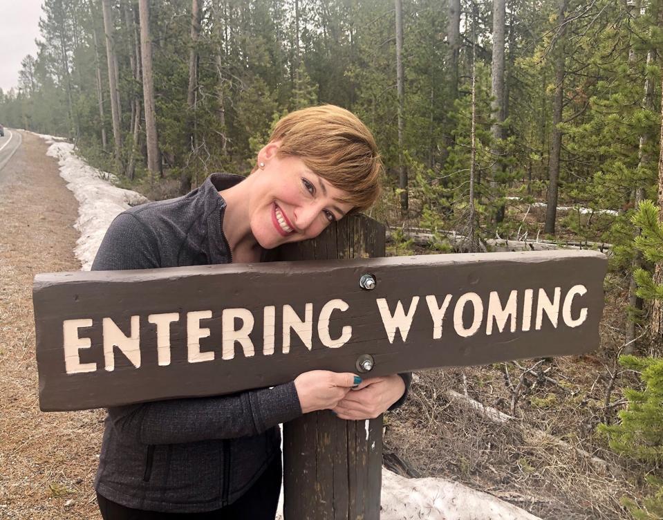 Pose panjang di depan tanda di Taman Nasional Yellowstone.