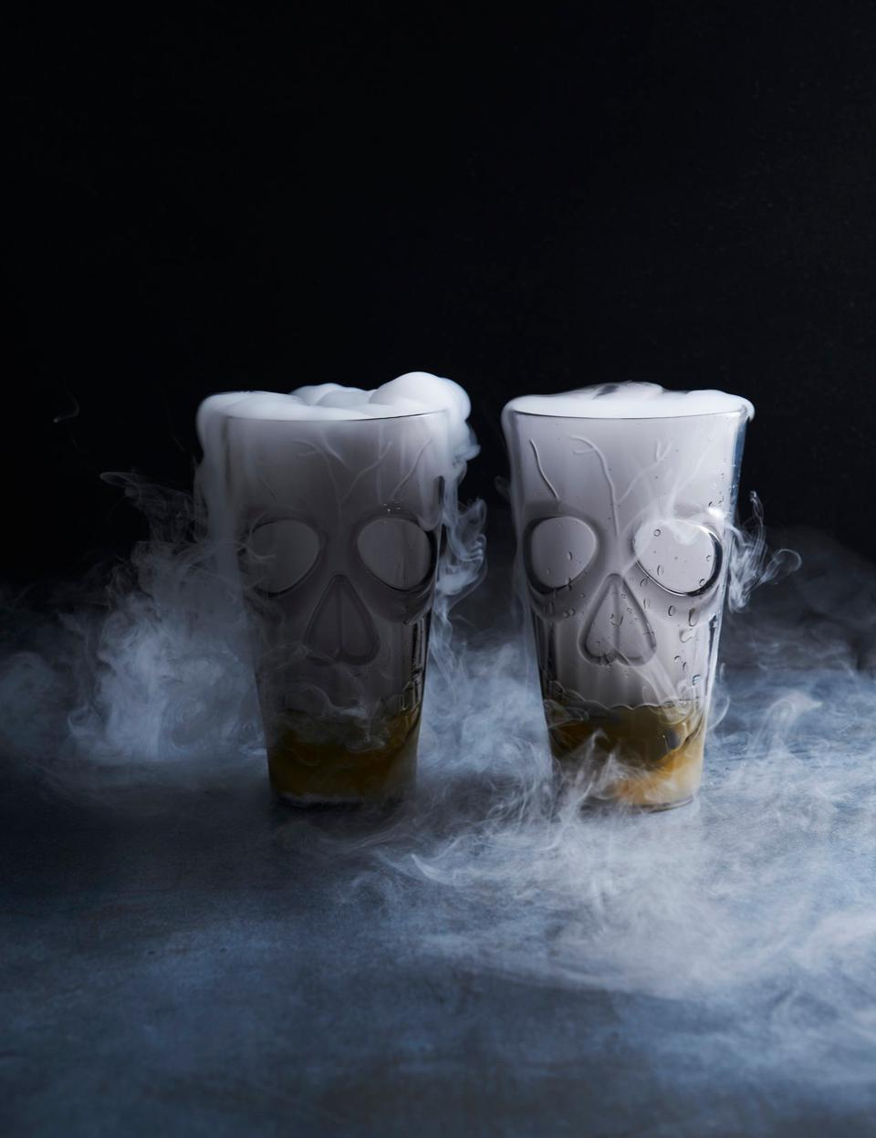 Two skull glasses with smoke coming out of them.