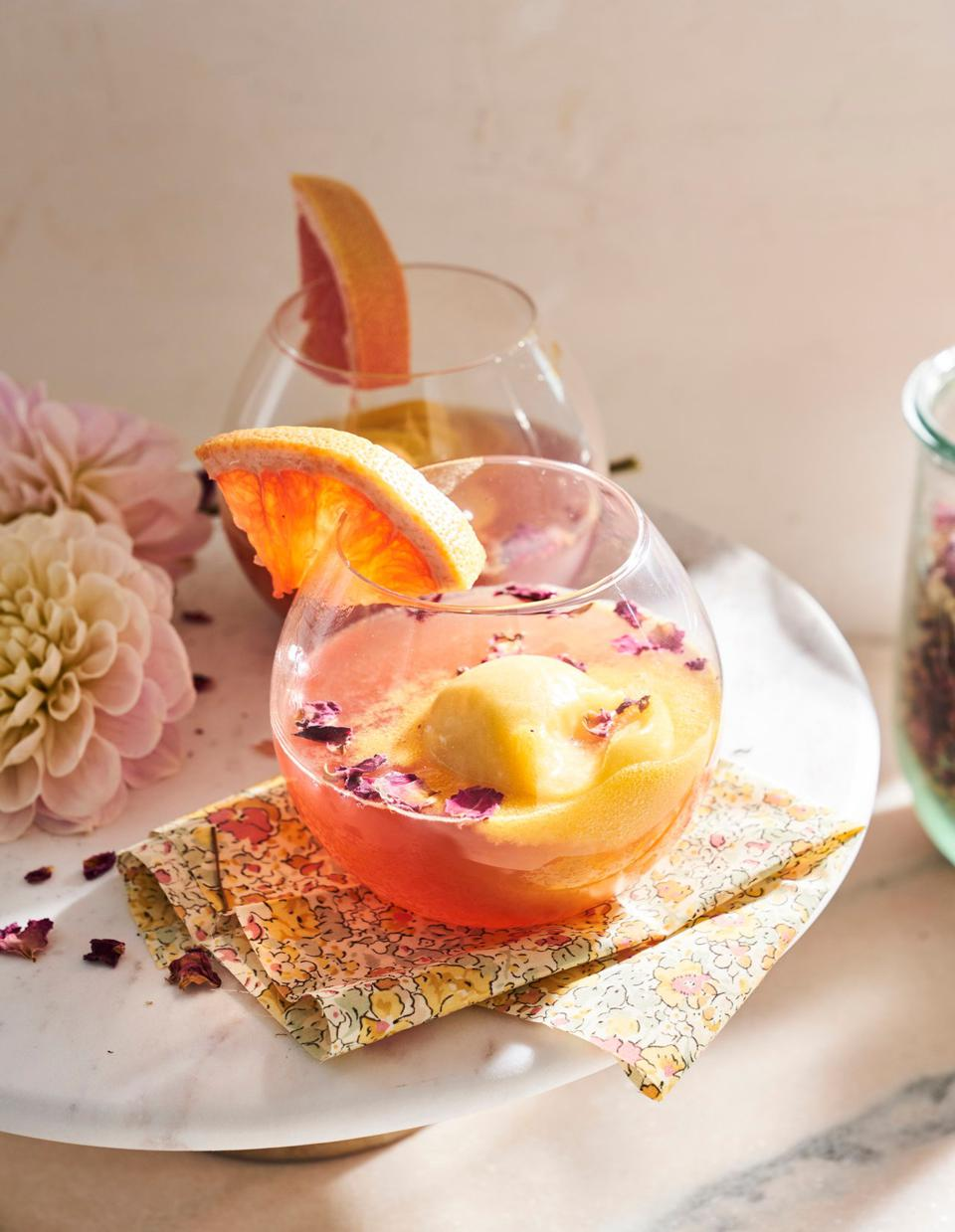 Cocktail in a large bowl-like glass with fruit garnishes.