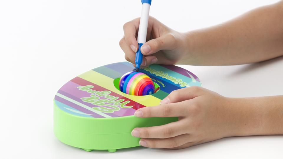 A child using the EggMazing egg decorator to color an Easter egg.