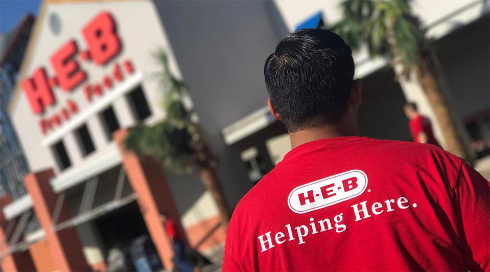 H-E-B employee with ″Helping Here″ shirt
