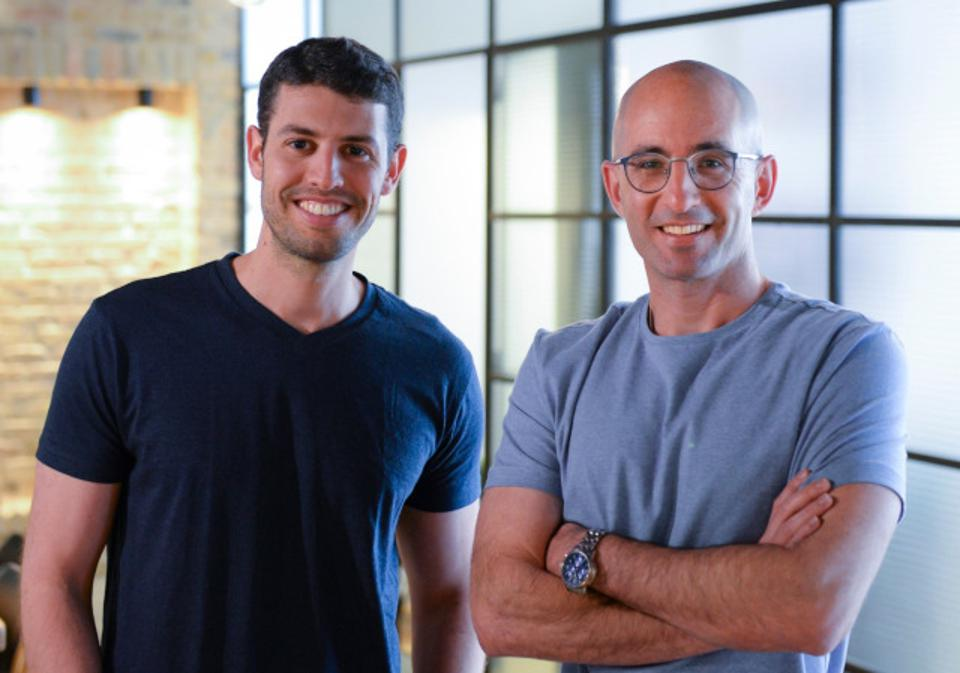 Run:AI co-founders, Omri Geller & Ronen Dar pictured waring t-shirts with arms folded and by the side smiling.