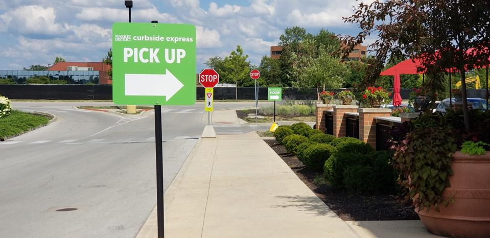sign outside grocery store directs shoppers where to go to pickup up at curbside the groceries they ordered online