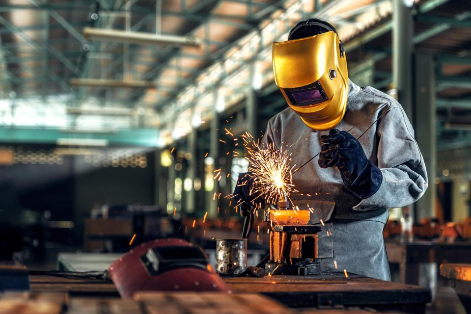 Worker welder working welding steel in industry with safety mask safety gloves and safety equipment. Worker welding concept.