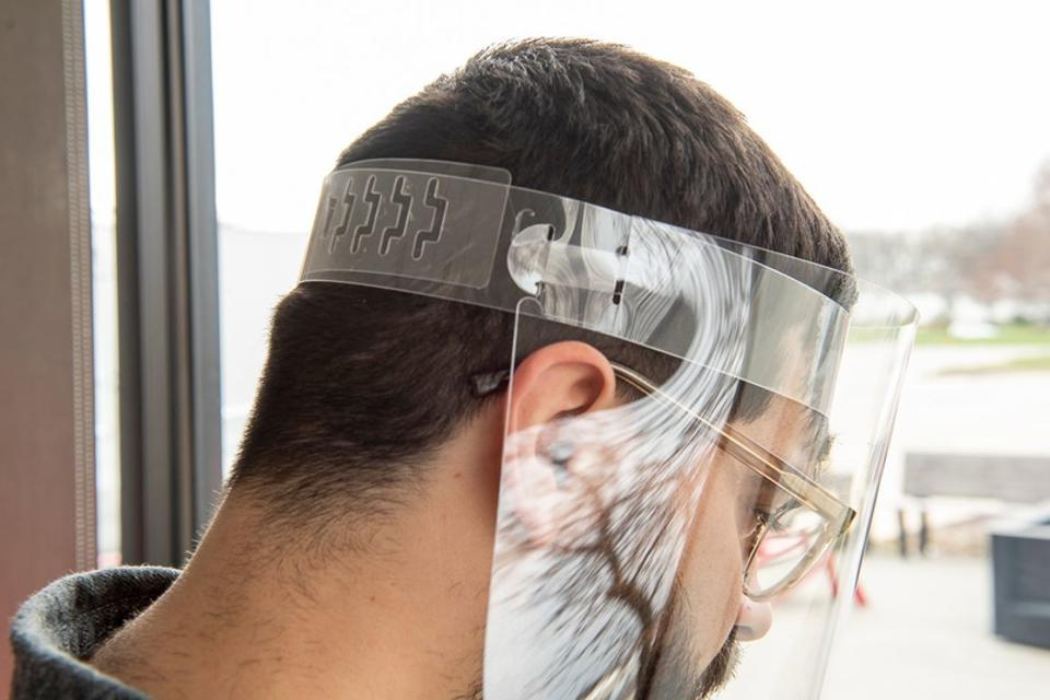 A man wears a face shield that is made via additive manufacturing technology.
