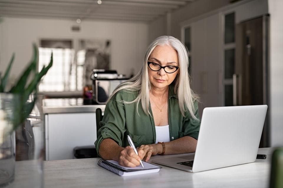 Senior woman working at home learning a new skill online.