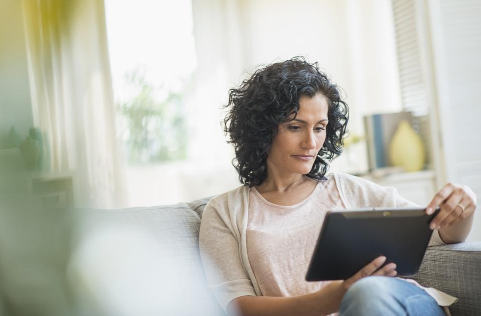 USA, New Jersey, Jersey City, Woman using digital tablet on sofa