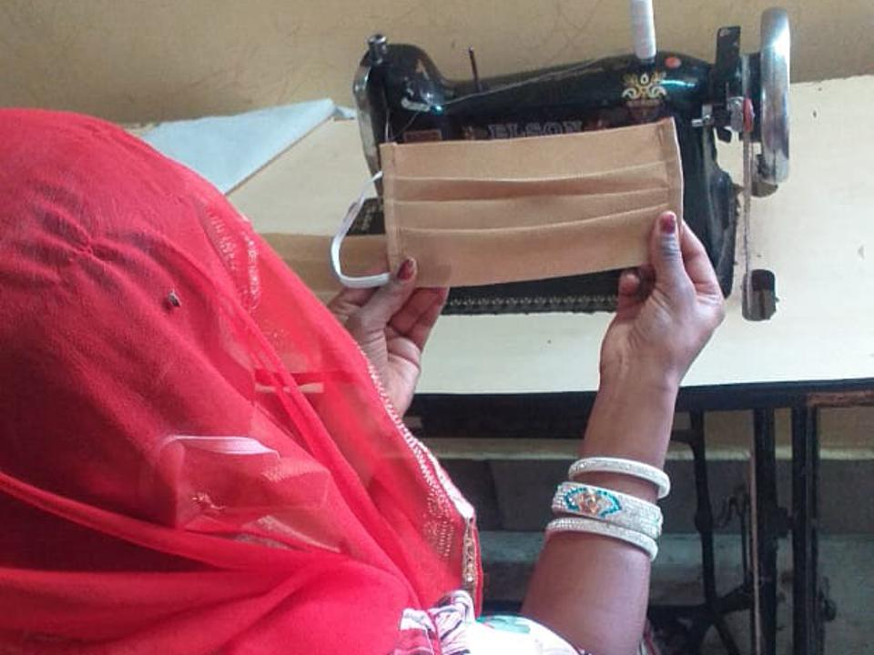 Refugee women sew face masks to sell outside of their settlement