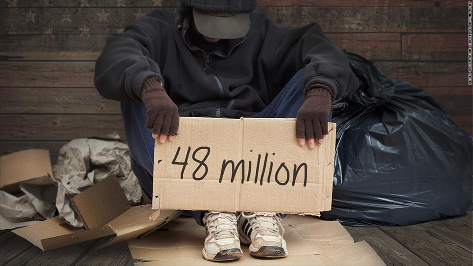 A homeless man holds a sign showing the number of Americans living in poverty