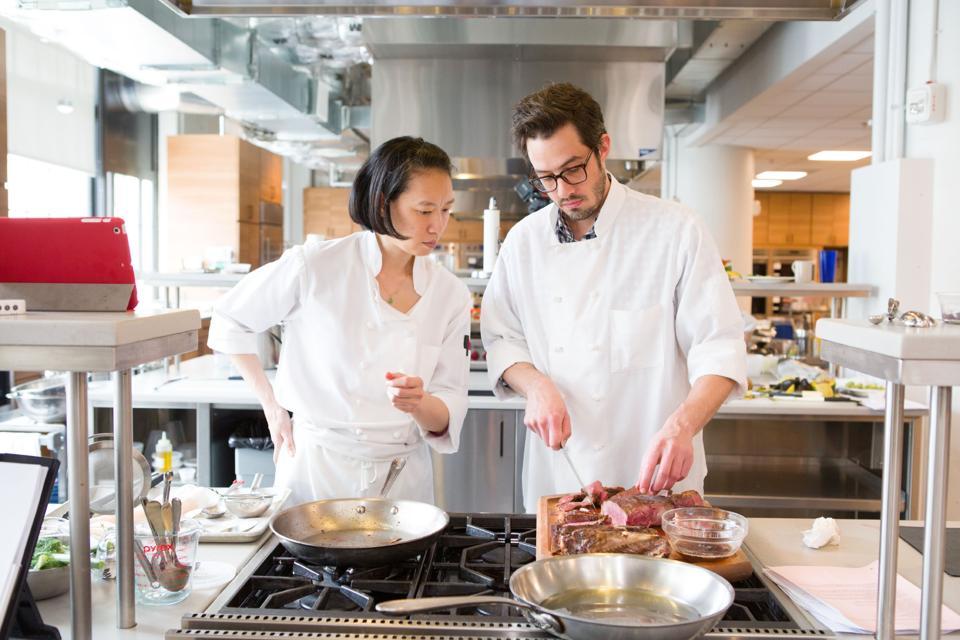 Two chefs cook a ribeye steak in America's Test Kitchen.