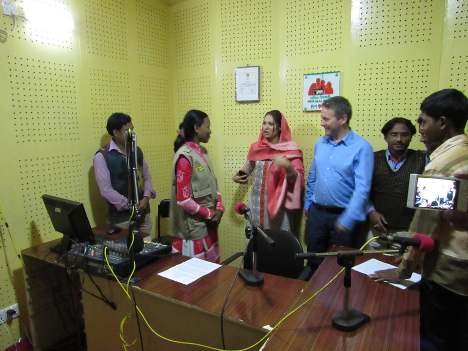 7 people in a recording studio, with bright lines and one person filming on a cellphone