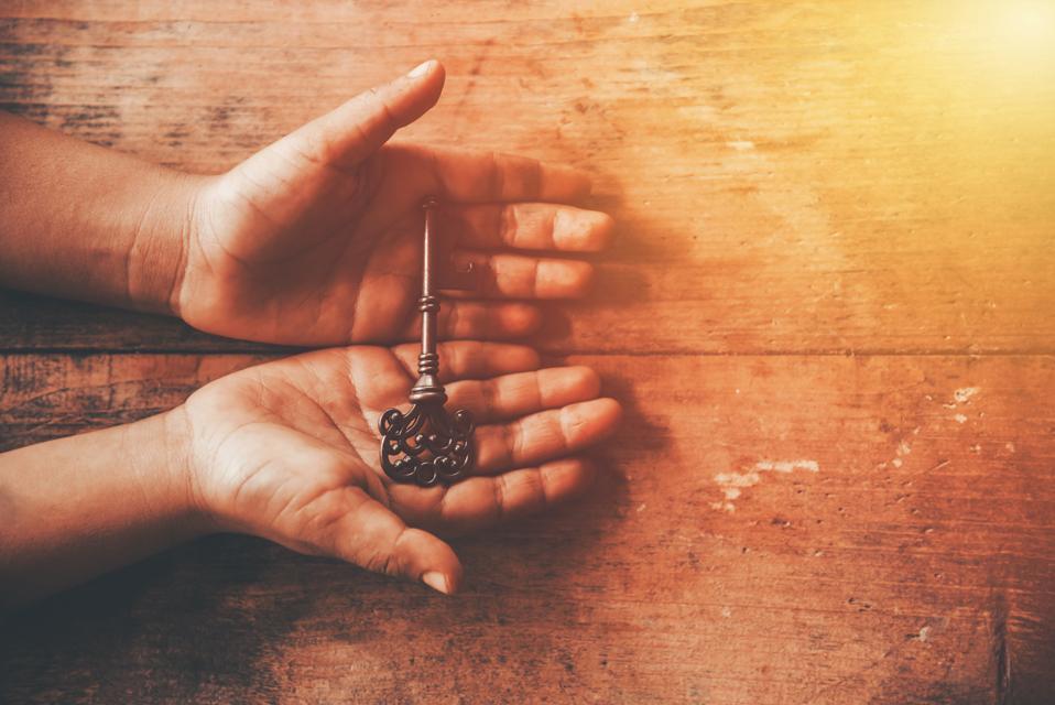 human hand holding a key