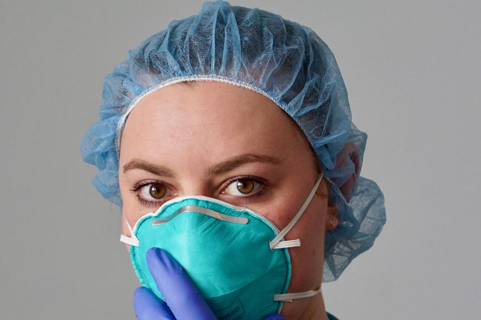 Close up of a female nurse putting on a respirator N95 mask to protect from airborne respiratory diseases such as the flu, coronavirus, ebola, TB, etc
