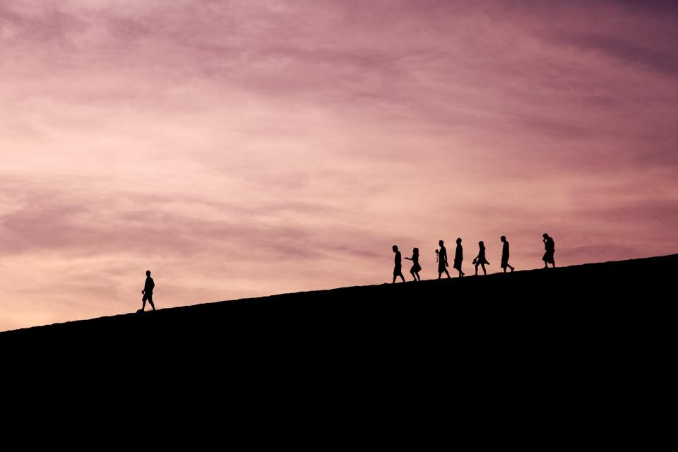 In a group of silhouetted people, one figure leads alone