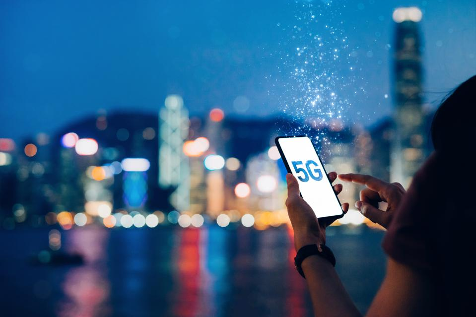 Young woman using smartphone against the iconic city skyline of Hong Kong by the promenade of Victoria Harbour at night, with the concept of 5G communications dissolved into light particles