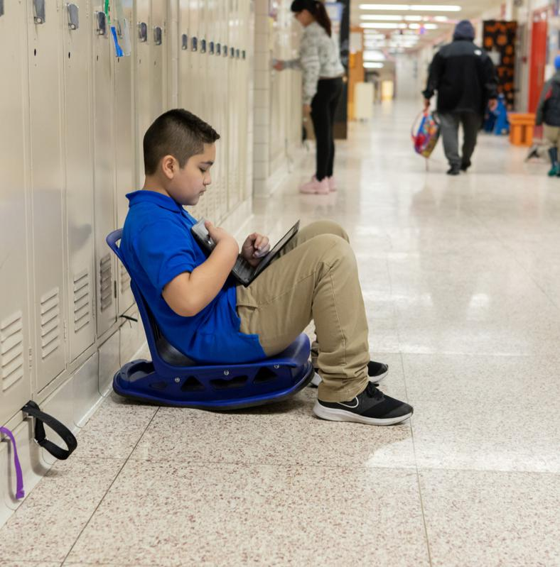 A boy in a blue polo works in the hall of his school, sitting back next to the lockers.