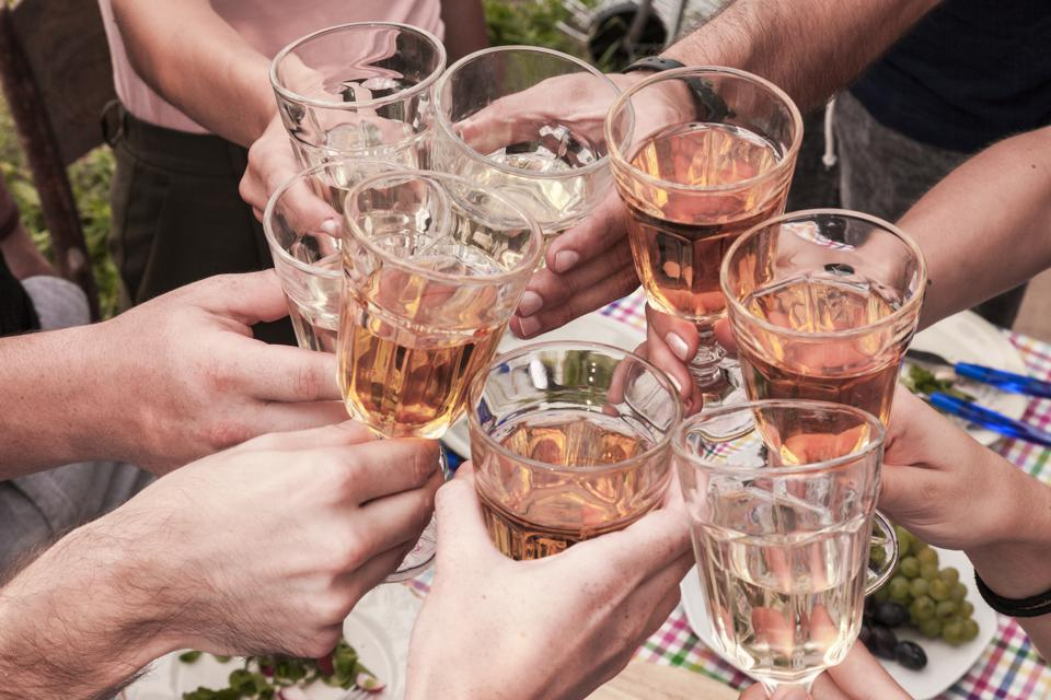 friends toasting with rose wine at a picnic table outdoor.