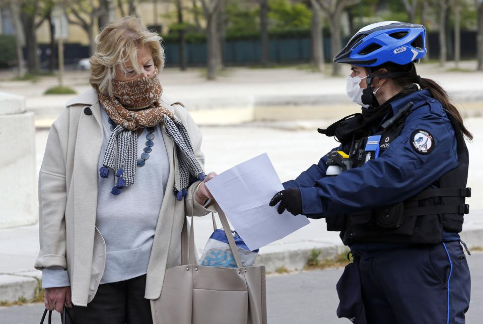 A policewoman checks a woman's authorization papers at the ″Champs de Mars″ next to the Eiffel tower on April 6, 2020.