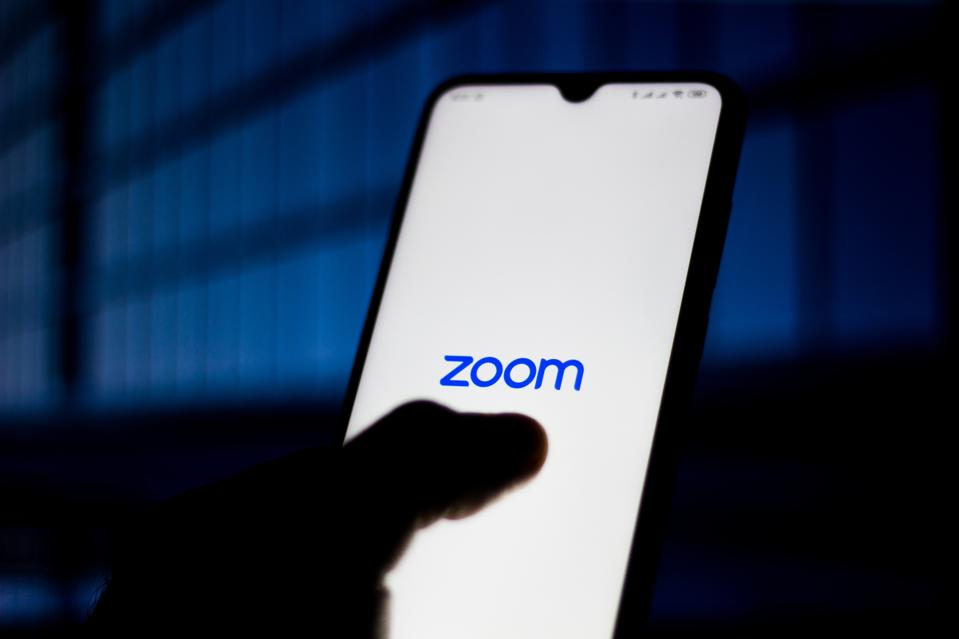 Zoom Meetings logo is seen on a smartphone