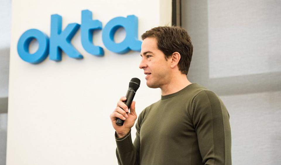 Okta CEO and co-founder, Todd McKinnon speaking into a microphone in front of his company's logo.