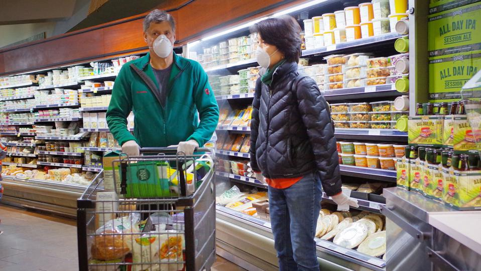 A man and a woman wearing face masks while shopping in a supermarket in Washington, D.C. in March.