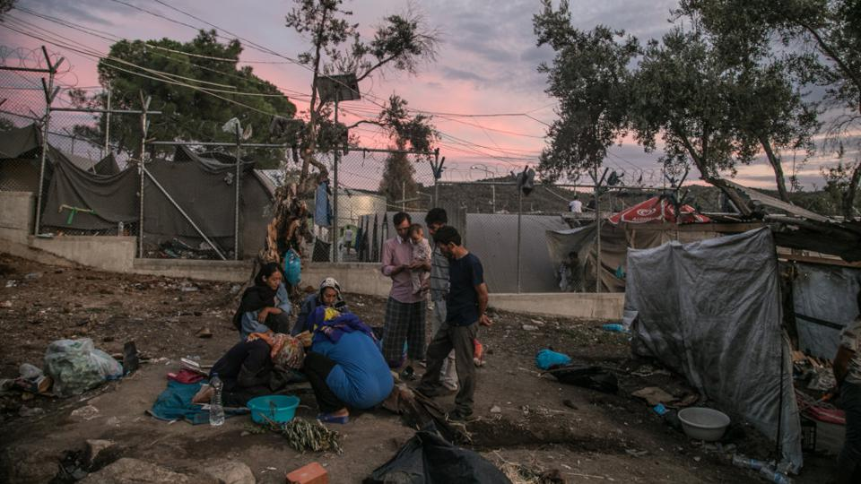 Refugees sitting next to a fence in the Moria detention center