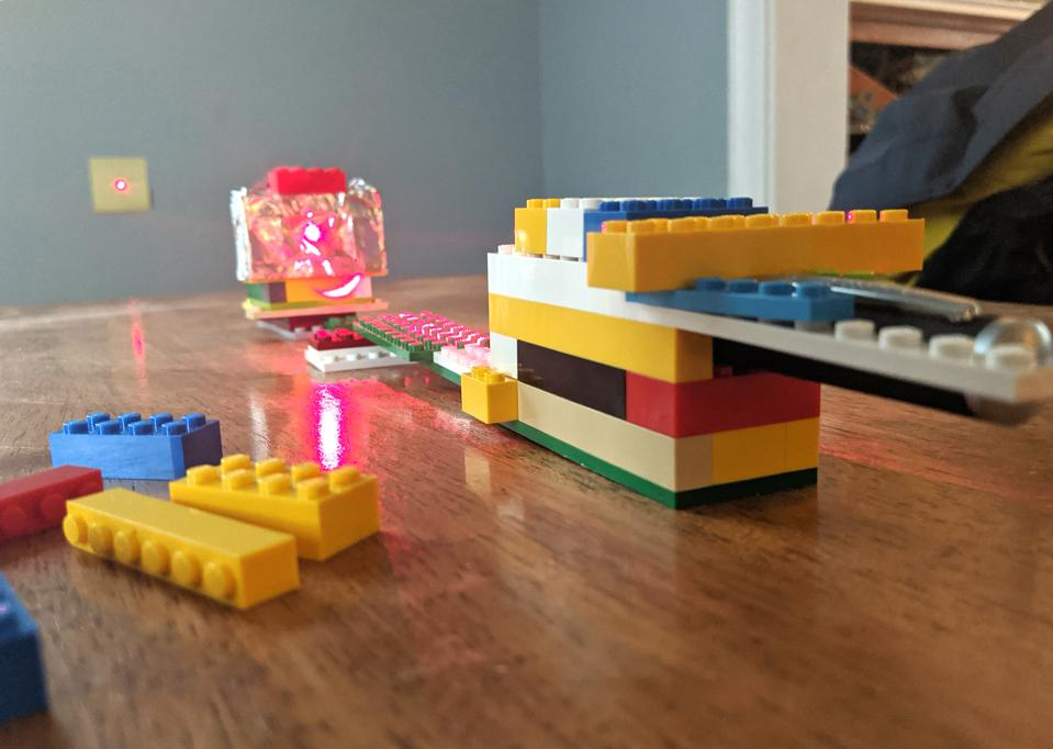 Laser pointer in a LEGO brick holder being used for an at-home diffraction experiment.