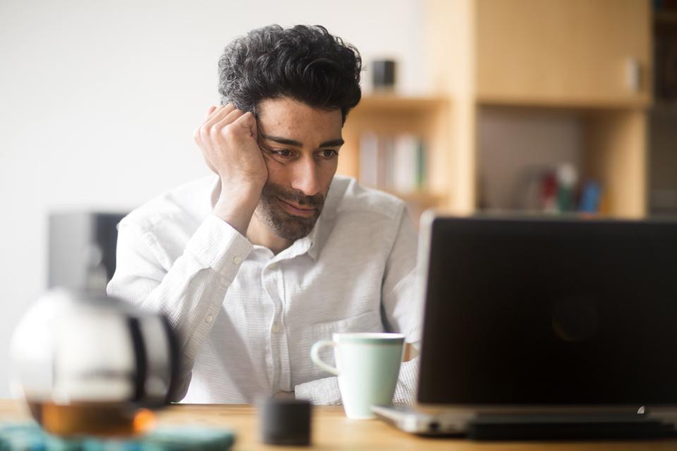 Portrait of businessman at desk looking at laptop