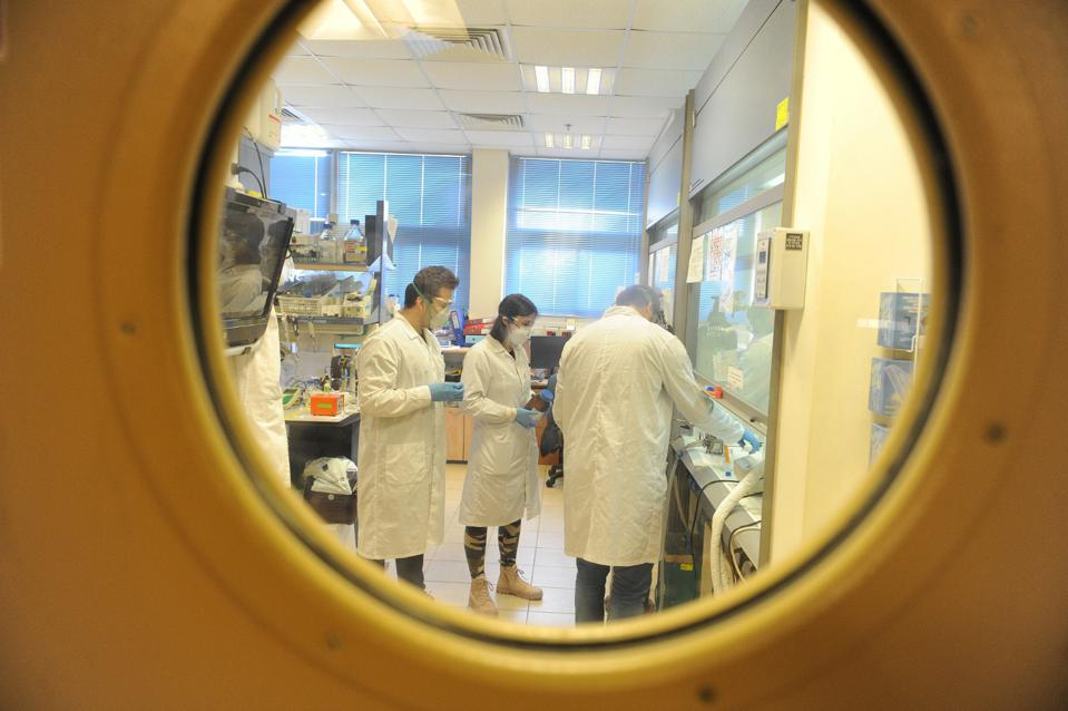Image take through a porthole in a laboratory door shows three scientists wearing masks working to find a COVID-19 vaccine