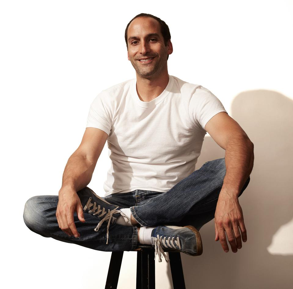 Grinning young man in jeans and white T-shirt sits cross-legged on bar stool
