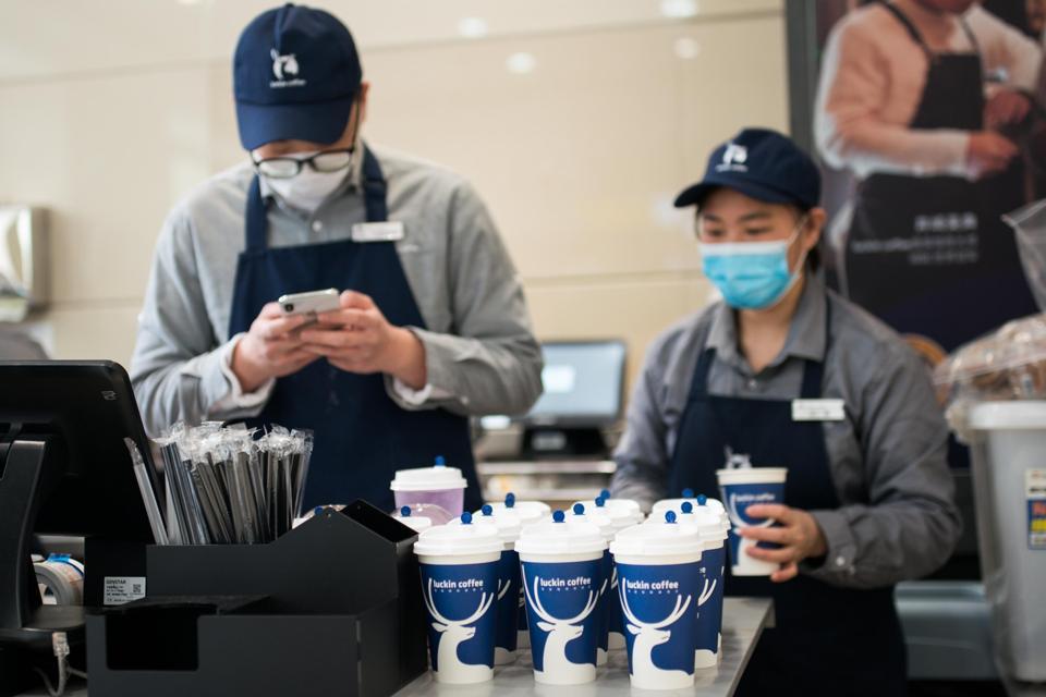 Staff wear protective masks at a Luckin Coffee shop