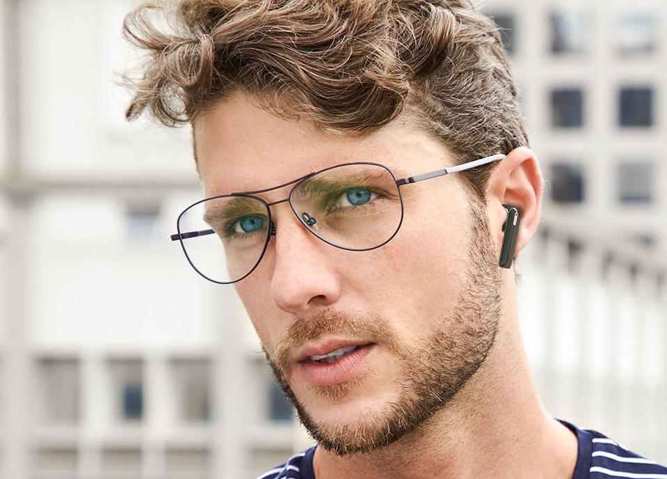 Man wearing black Tronsmart Onyx Ace earbuds