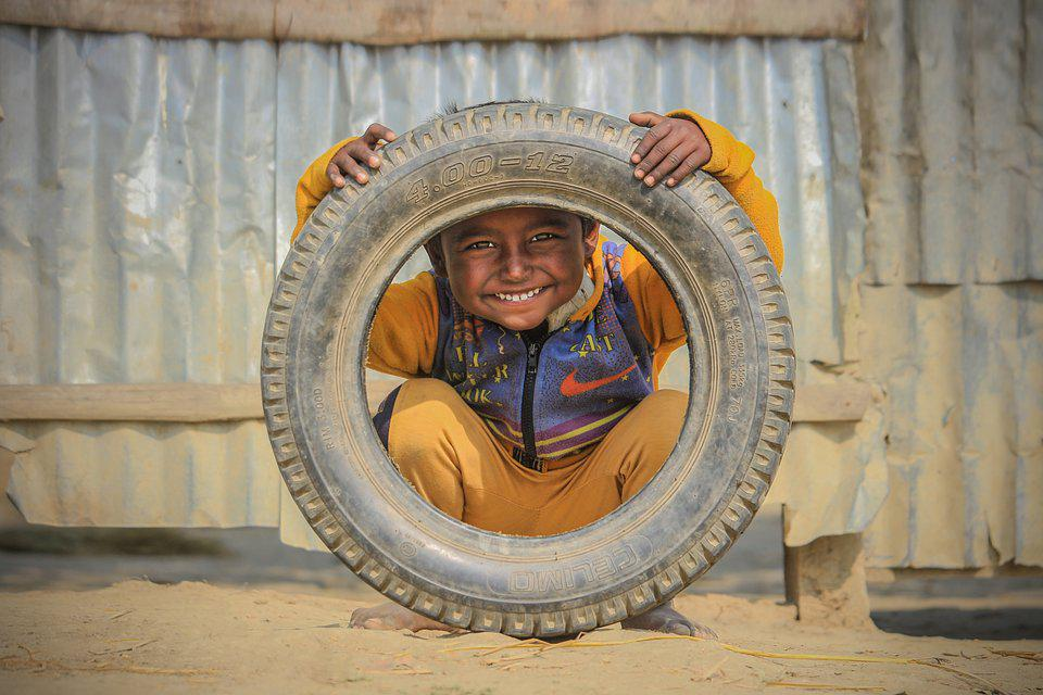 little boy playing with tire