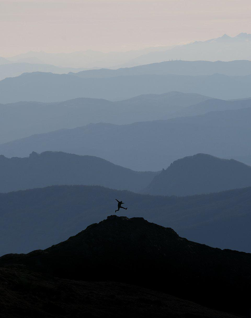 Man jumping high on the Appennine mountains in Italy