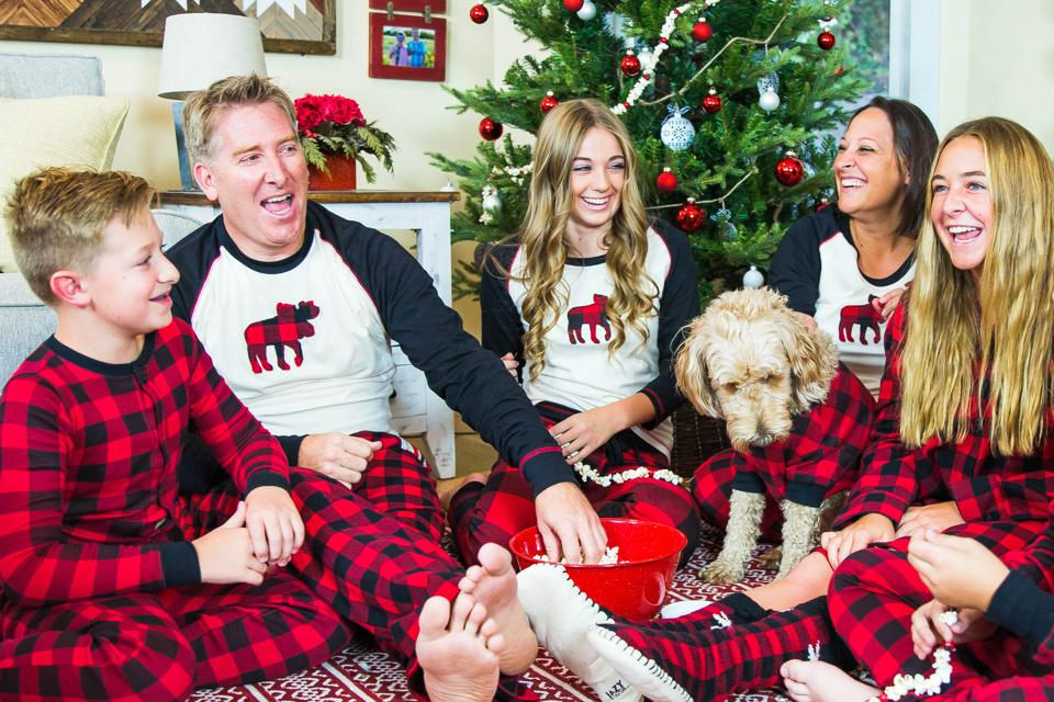A family and their dog relaxes in matching Lazy One pajamas